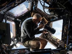 "Photographing Earth from the Cupola on the International Space Station: ""The image shows astronaut and flight engineer Chris Cassidy pointing a Nikon DSLR and 400mm lens out one of the Cupola's windows to photograph some location on Earth 250 miles below him."""