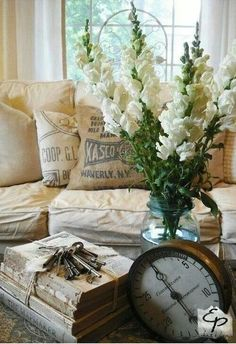 Flour sacks as pillows and old books wrapped in cord with keys and large clock on coffee table.