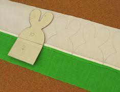 m primeiro lugar você vai imprimir o molde que está no link acima e passar para um papel durinho, que pode ser cartolina, um pedaço de caixa de embalagem ou papel cartão.  Depois vai cortar duas barras de tecido branco com 10 cm para a parte superior dos coelhos.  E duas barras de 7 cm de tecido estampado e colorido para a parte debaixodos coelhos (O tecido estampado vai ficar do lado de fora do cesto, e o colorido no lado interno).  A largura das barras de tecido, ou seja, o comprimento… Felt Crafts Diy, Homemade Crafts, Easter Crafts, Puff Quilt, Easy Sewing Projects, Pin Cushions, Easter Bunny, Hand Embroidery, Quilts
