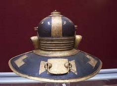 """The famous Niedermörmter Roman helmet of the 3rd century BC. Back view. This style of helmet with hinged cheek pieces and a large neck protection was found in the river Rhine (now in the Mainz museum). It is a Weisenau type. Along with the elaborate applique and perforated brow, this helmet sports a unique design element on the crown: what are described as either """"Mice and cheese"""" or """"Mice and bread""""."""