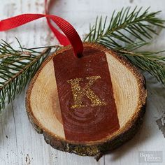 Trim the tree with stunning personalized ornaments. To create, simply take cut log sections and paint a strip down the middle. Let dry. Using a stencil, paint a letter with gold glitter paint over the strip. Finally, drill a hole through the top and tie with ribbon.