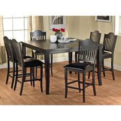 Give your dining room an elegant new look with this black high dining set, which includes a table and six stools with backs. The chairs are upholstered in faux leather to keep you and your guests comfortable and to add to the set's stylish look.