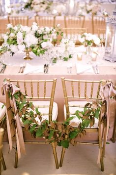 Such a cute idea to have a garland on the bride and grooms chairs at the reception table