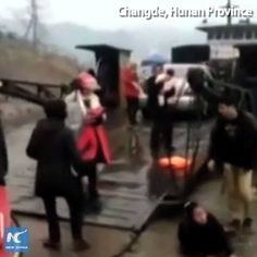 Desperate dad throws baby to strangers after he drove the family car into a river in Changde, Hunan Province.