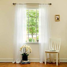 Sheer white drapes not only let natural light in, but they can also trick your eyes into thinking your home has more depth.