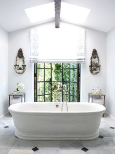 Light-filled white bathroom with antique wall sconces and open windows