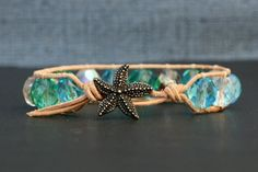 This single wrap bracelet features 10mm czech glass faceted fire-polished beads in sea glass shades stitched to natural color leather with starfish closure