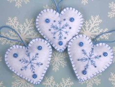 Handmade snowflake heart Christmas ornaments.  Three white felt hanging hearts, hand embroidered with a snowflake pattern in light blue, finished with three tiny buttons and a loop for hanging. Each of the 3 felt hearts has a different snowflake pattern.  Height 7cm/2.75 inches  White with light blue embroidery and buttons. The listing is for 3 hearts.  You can see these snowflake ornaments in other colours, and more heart ornaments here…