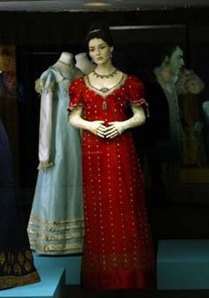 Image: Persuasion display case, with original blue silk gown shown next to red patterned silk gown as worn in the film