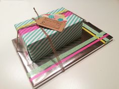 Baby shower present. Silver wrapping papier, pink, yellow, mint, washi tape, bakery twine, label, stamps, colorful fabrics