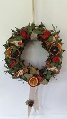 Rosca hecha con ramas de ramas de eucalipto,  naranjas, tomates secos, canela