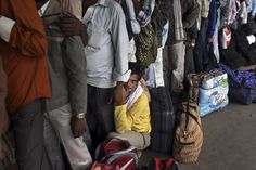 TAKE A LOAD OFF: A man rested in a line of passengers waiting to board a train in New Delhi, India, Thursday. (Tsering Topgyal/Associated Pr...