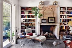 Bookshelves flank a stone fireplace in the library of decorator Isabel López-Quesada's Madrid home.
