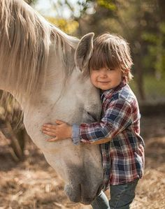 Tiny boy hugging a horse