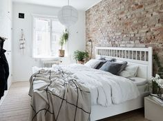 A few design ideas for a small bedroom can be to include a brick wall as a focal wall (you can use either true brick or a wallpaper) and pair it with white modern furniture. I love how contemporary this look is, especially with black and white artwork! Small Master Bedroom, Home Bedroom, Modern Bedroom, Bedroom Decor, Bedroom Ideas, Contemporary Bedroom, Bedroom Lighting, Bedroom Chandeliers, Master Suite