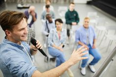 Successful business coach presenting sales strategy by seventyfourimages. Positive successful business coach in casual shirt gesturing hand and speaking into microphone while presenting sales.