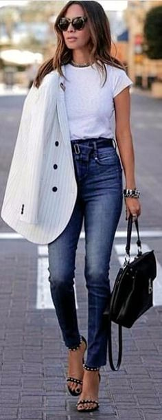 #spring #outfits woman wearing cap-sleeved shirt and blue-washed jeans holding handbag. Pic by @fashion__times__