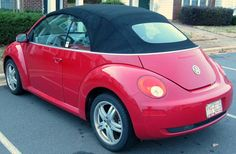 Red convertible Volkswagon Beetle with license plate that says lilal