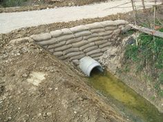 They look like sandbags but are actually hessian bags filled with wet concrete and pinned together with steel rods making a good, solid retaining wall.