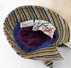 Lindo M.r John Jr. split sombrero tejido. Rayas de neón de azul, limón, lavanda, mandarina, gris y negro crean este sombrero relajado Linda corona asimétrica. Corona de profunda, 2 1/2 pulgada quema ala con una división de lado acentuada con un arco grande. Interior es forrado con un acetato de lavanda y adornado con una cinta del grosgrain azul real. La etiqueta es el Sr. John Jr con una etiqueta de la tienda de Lázaro en Roanoke va Esta etiqueta del señor John fue utilizada a partir l...