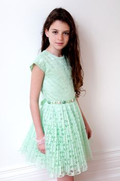 Your little lady will look all grown up wearing this David Charles party dress, the mint pleated lace with belt. This beautifully sophisticated girl's special occasion dress is made from a luxurious mint fabric underlay and a mint lace overlay. The bodice is fitted with elegant capped sleeves, and a magnificent embellished belt with stones and jewels separates the pleated skirt that sits just above the knee. The belt ties with a ribbon bow giving the dress a stylish appearance from the…