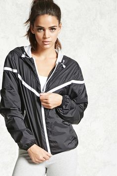 A woven windbreaker jacket with a zippered front, a toggled drawstring hood, mesh lining, chevron stripe along front and back, long sleeves, zippered pockets, an interior pocket, and elasticized hem and cuffs.