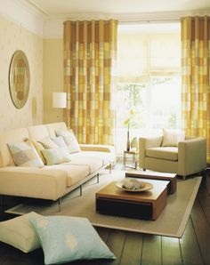 A modern and airy living room with solid hardwood flooring in a rich dark stain and deep furniture that is perfect for curling up in. The modular coffee table can be expanded if more space is needed. The furniture is in a light beige with yellow tones, and pastels in the throw pillows and curtains add a subtle, chic dash of color.