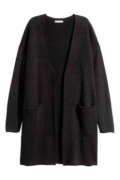 Casaco de malha comprido: Casaco comprido em malha macia com uma percentagem de lã mohair. Tem bolsos à frente e não tem botões.