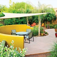 A free-form hardscape, shade sail, airy plants, a circular firepit make this garden the ideal place for entertaining.