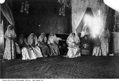 A Qajar Prince, most probably Ahmad Shah is sitting in the middle of Qajar Harem Ladies. The photograph is possibly taken in Golestan Palace which was the residence of the Qajar royal family.