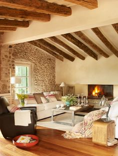 Love the beamed ceiling, exposed stone wall and floors