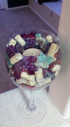 wine inspired candle i made for my new place using a large decorative wine goblet, small bunches of colored grapes, colored glass rocks and wine bottle corks....all items purchased at michaels #candlemaking