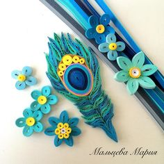 Quilled paper art peacock feather and flowers.