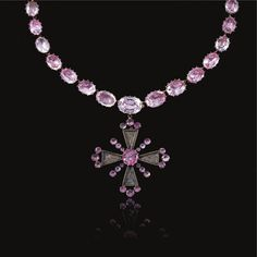Hesketh Pink Topaz Riviere. A graduated rivière of oval pink foil back topaz mounted in cut-down collets, suspending a detachable Maltese Cross pendant , the arms each set with a glazed locket of hair, embellished with circular topaz accents,
