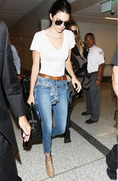 Kendall Jenner wears a white t-shirt tucked into belted jeans with a plaid shirt tied around the waist and snakeskin boots