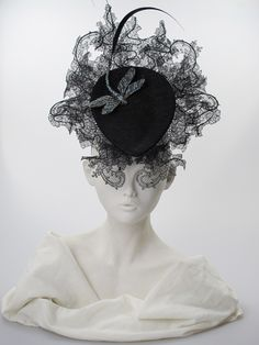 Philip Treacy. Black teardrop hat with ornate lace and dragonfly.