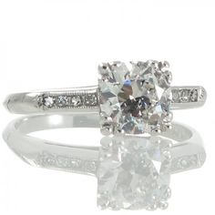 A platinum solitaire style ring featuring a transition cut diamond of estimated weight 1.15ct set in a raised four corner claw box style mount channel set to each shoulder with four single cut diamonds with a millegrain surround all to a plain polished knife edged band. #RutherfordJewellery #Melbourne
