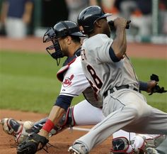 Cleveland Indians catcher Yan Gomes, left, drops the ball as Detroit Tigers' Torii Hunter scores in the first inning of a baseball game on Wednesday, May...