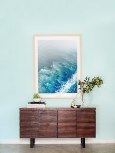 """For the makeover, Whitney explains, """"We wanted to make sure the white walls were filled with tons of artwork and that the furniture was cozy and inviting."""" Orlando responded by painting the walls a cheerful Robin's-egg blue and adding beachy accents like this oversized ocean print and warm wooden console."""