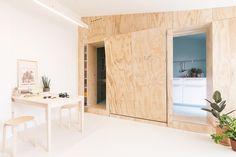 """IDEE SALVA-SPAZIO PER UNA CASA EXTRA-SMALL: AMPLIFICARE LA LUCE Le zone di servizio sono concepite come """"due scatole monocromatiche azzurre"""", mentre la zona giorno è caratterizzata da superfici bianche per amplificare la luminosità e far risaltare la matericità delle pareti in legno. Sospensione al neon su disegno studioWOK, tavolo e sgabelli IKEA."""