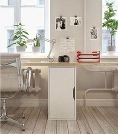 długie biurko z drewnianym blatem i białą szafką pod oknem w salonie
