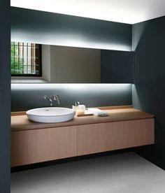 Baño de color gris iluminado por luces led colocadas detrás del espejo. Mobiliario de color beige