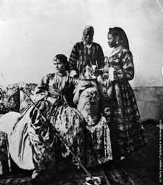 A white lady in crinoline, attended by two women, in a harem in Cairo, ca. 1870