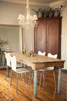 Graceful elegant dining room with wood floor and two toned white and wood table with contemporary chairs and vintage chandelier, large silver mirror reflects space, watering cans a top a cherry wood armoire pull together a strangely classic yet modern ethereal space