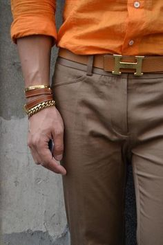 Orange shirt works very well with mocha colored pants.  Caramel and gold accessories (especially the Hermes belt) pull it all together.