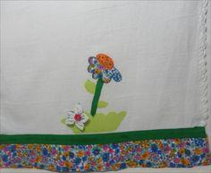Em sacaria, com patch apliquê, fuxico de flor com botão em formato de flor, viés personalizado e barrinha de tecido, crochê. R$ 26,25