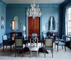 Warm wood accents and mismatched chairs update a formal dining room.   Blue walls and painted trims add a fresh spin to this eclectic dining room. A sparkling glossy finish on the crown mouldings draws the eye upwards, showcasing this room's height. The blue hue is carried onto the uphostery and vases for a saturated look