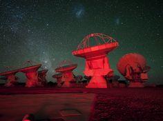 Este impressionante wallpaper do espaço revela as antenas do ALMA banhadas a luz vermelha. Aparecendo ao fundo estão a Via Láctea à esquerda e as Nuvens de Magalhães no topo. Esta imagem foi lançada a 5 de março de 2013.