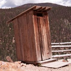 An outhouse balances precariously on the edge of a cliff.