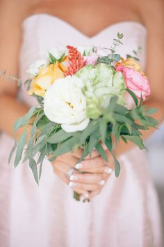 Bridesmaid in baby pink dress holding colurful bouquet   Photography: Jillian Mitchell - jillianmitchell.net